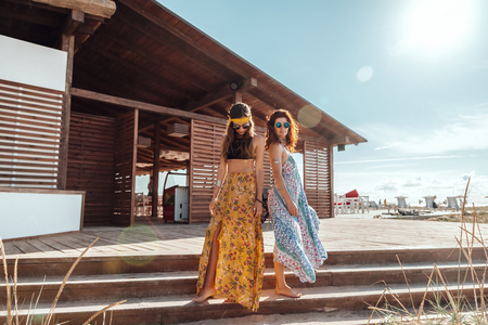 Two boho friends (girls) wearing floral maxi dress and skirt relaxing on the beach. Bohemian clothing style. Standard-Bild