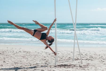 Pole dance outdoors. Young slim girl doing poledance on the beach over sea.