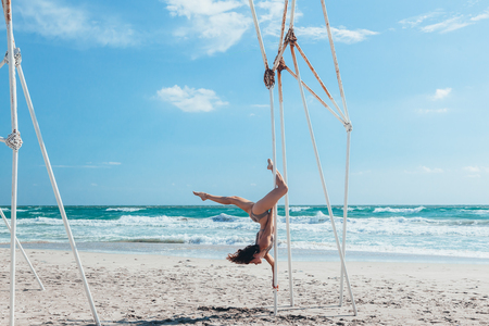 Pole dance outdoors. Young slim girl doing poledance on the beach over sea.