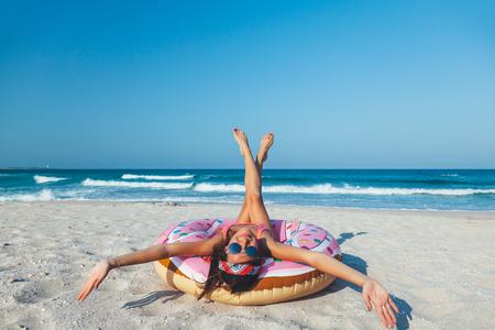 Meisje het ontspannen met doughnutlila op het strand. Spelen met opblaasbare ring. Zomervakantie idyllisch op een tropisch eiland.