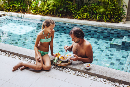 Dad with child relaxing and having breakfast by the hotel pool. Exotic summer diet. Tropical beach lifestyle.