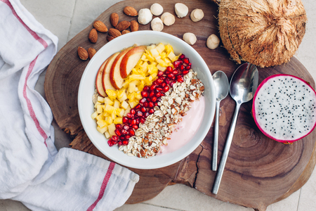 Smoothie bowl with colorful tropical fruits on wooden serving tray, top view from above. Summer healthy diet, vegan breakfast. Banco de Imagens