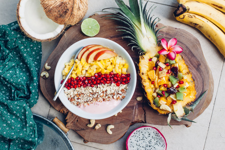 Smoothie bowl with colorful tropical fruits on wooden serving tray, top view from above. Summer healthy diet, vegan breakfast. Stockfoto