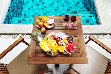 Tropical fruit plate by the hotel pool for two, top view from above. Summer healthy diet, vegan breakfast. Tasty vacation concept.
