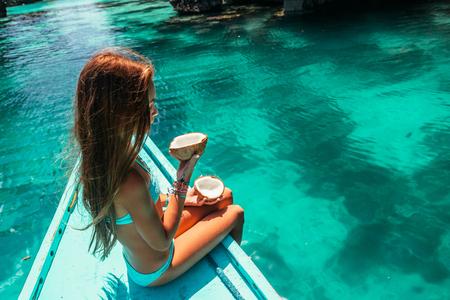 보트에서 휴식 하 고 맑은 바다 물 위에 코코넛을 먹는 어린 소녀. 아시아 여행 투어 : El Nido, Palawan, Philippines. 스톡 콘텐츠