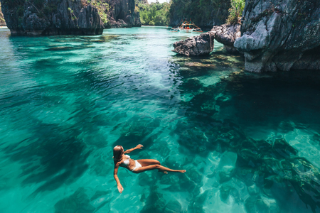 Young woman swimming in clear sea water in lagoon and looking at beautiful landscape. Travelling tour in Asia: El Nido, Palawan, Philippines.