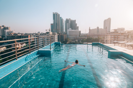 Young woman swimming and enjoying the morning view from roof top infinity pool in Bangkok, Thailand Archivio Fotografico