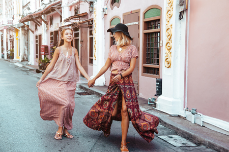 Boho mom with daughter in maxi skirt walking on the city street. Bohemian family look. Travelling in Phuket Old Town in Thailand. Standard-Bild - 98176262
