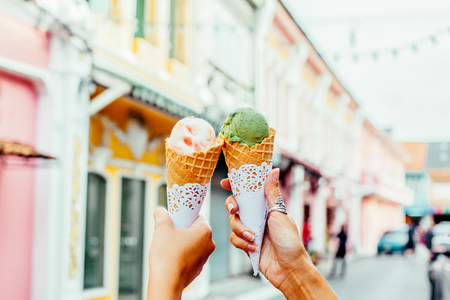 Two hands holding colorful ice cream in cone over blurred street background. Stock Photo