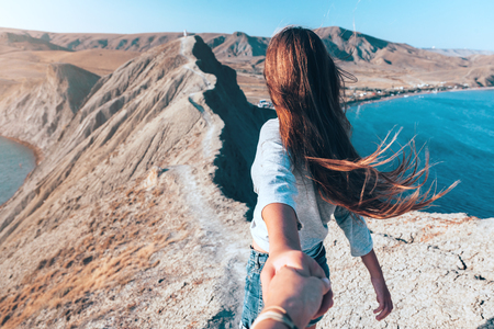 Girl walking on the mountain top over blue sea view. Follow me - POV.