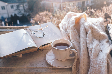 Opened book, cup of tea, glasses and knitted sweater in warm sunlight on the window sill. Cozy spring weekend concept. The text on pages is not recognizable. 스톡 콘텐츠