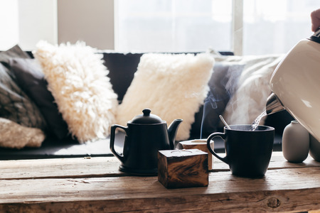 Still life details of nordic living room. Pouring tea with steam on a rustic coffee table over black sofa in morning sunlight. Cozy winter concept in scandinavian home interior. Stock fotó