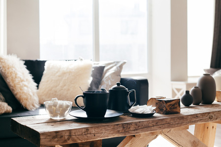 Still life details of nordic living room. Cup of hot tea with steam on a rustic coffee table over black sofa in morning sunlight. Cozy winter concept in scandinavian home interior. Stock Photo