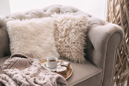 Still life details of nordic living room. Coffee and sweater on the sofa with fur cushions. Cozy winter scene in Scandinavian interior.