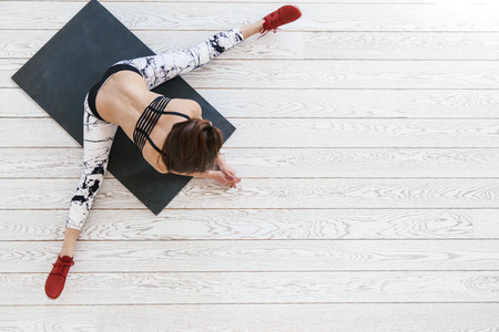 Young beautiful girl wearing fashion sports wear doing pilates exercise on black mat on white wooden floor in bright gym, top view overhead Stock Photo