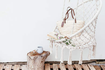 Summer hygge scene with hammock chair, book and flowers. Cozy place for weekend relax in the garden. Stok Fotoğraf - 103174282