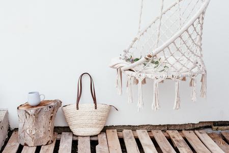 Zomerhygge-scène met hangstoel, boek en bloemen. Gezellige plek om weekend te relaxen in de tuin.