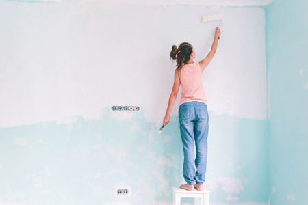 Preteen child painting the wall in her room in blue and white colors. Young girl making interior renovation at home.