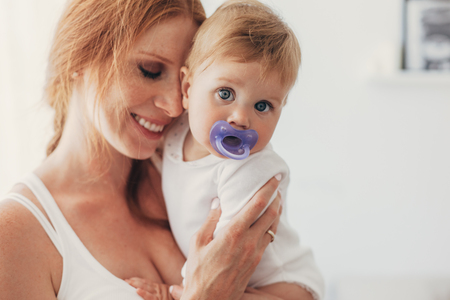 Portrait of beautiful loving mom holding on hands her 8 months old baby with nipple in bedroom
