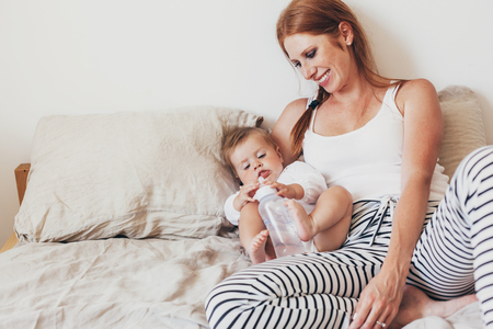 Portrait of beautiful loving mom feeding her 8 months old baby with bottle in bedroom