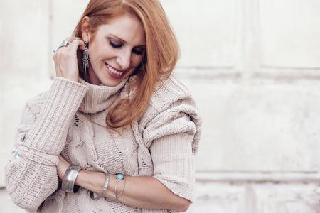 Biżuteria boho na modelu: etniczne pierścionki, bransoletki i kolczyki. Piękna kobieta ubrana w ciepły wełniany sweter i modną biżuterię. Zdjęcie uliczne w pastelowej tonacji.