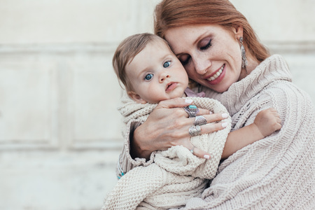 Portrait of beautiful mom holding on hands her 8 months old baby. Both dressed in warm winter knitted clothing.