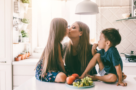 Mom with her two children sitting on the kitchen table and eating fruits together. Mother with daughter and toddler son having breakfast at home. Happy lifestyle family moments. Banco de Imagens
