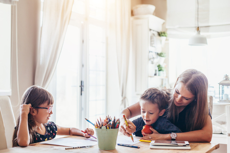 Mamá jugando con su hijo de 2 años y su hija en edad preescolar en casa. Madre dibujando con lápices junto con los niños.