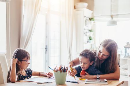 Mutter spielt mit ihrem 2 Jahre alten Sohn und ihrer Tochter im Vorschulalter zu Hause. Mutter, die mit Stiften zusammen mit Kindern zeichnet.