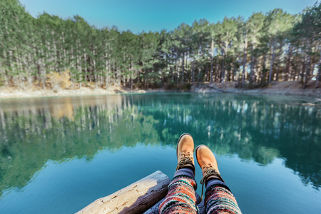 Woman relaxing in by the lake in the forest, POV view of legs in trekking boots. Hiking in cold season. Wanderlust concept scene. Stock Photo