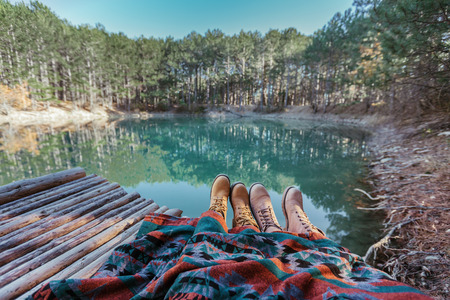 Couple or friends relaxing in by the lake in the forest, POV view of legs in trekking boots. Hiking in cold season. Wanderlust concept scene. Foto de archivo - 111345222