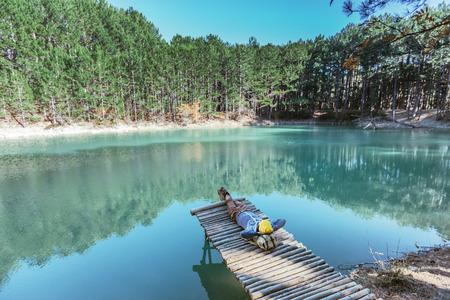 Man traveler resting on wooden peer on blue lake in pine woods. Hiking in cold season. Wanderlust concept scene. 스톡 콘텐츠