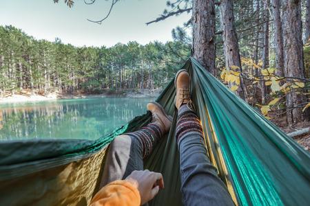 Frau, die sich in der Hängematte am See im Wald entspannt, POV-Blick auf die Beine in Trekkingstiefeln. Wandern in der kalten Jahreszeit. Wanderlust-Konzeptszene.