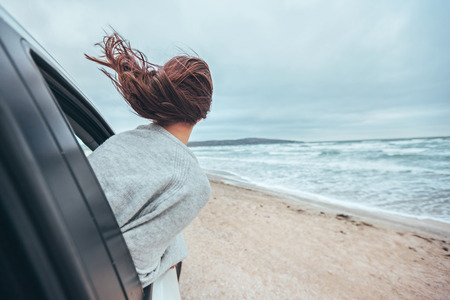 Young girl watching sea waves outside. Weekend trip in bad rainy weather. Dramatic winter travel concept.