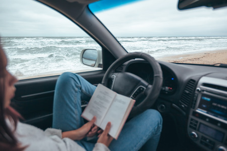 Young girl reading in car over sea waves outside. Weekend trip in bad rainy weather. Dramatic winter travel concept.