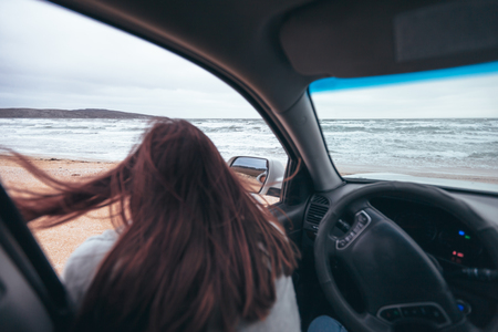 Young girl relaxing in car and looking at sea waves outside. Weekend trip in bad rainy weather. Dramatic winter travel concept.