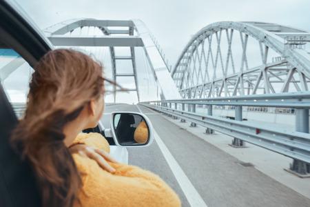Rear view of pre teen girl in car looking forward on a bridge at weekend road trip Stock Photo