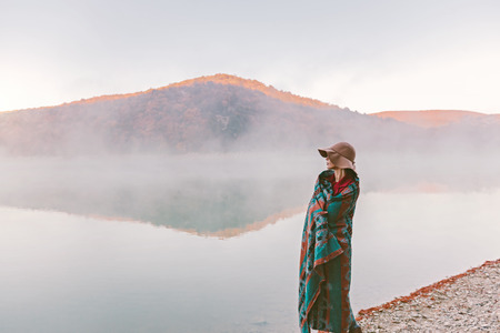 Girl wrapped in warm boho blanket standing and looking at foggy sunrise. Cold morning by the lake.