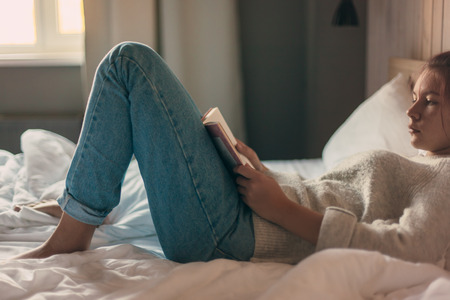 Teen girl in sweater reading a book in a hotel bedroom in the morning Foto de archivo