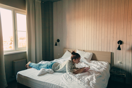 Teen girl in sweater reading a book in a hotel bedroom in the morning 免版税图像