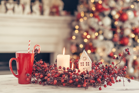 Velas y decoración navideña en la mesa sobre fondo de luces de noche borrosa