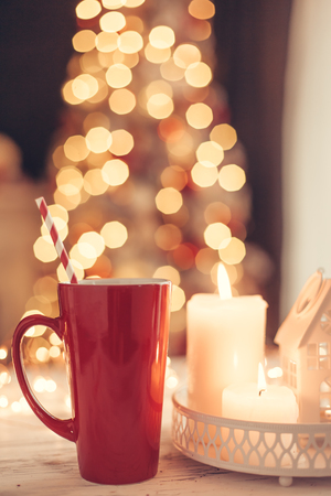 Candles and Christmas decoration on table over blurred evening lights background