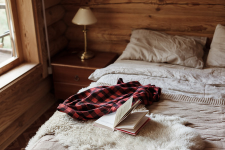 Rustic interior of log cabin bedroom with bed by big window. Opened book on sheep rug. Warm and cozy weekend morning in hotel. Reklamní fotografie - 111901867