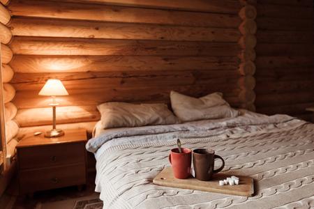 Interior rústico del dormitorio de la cabaña de troncos. Cama acogedora junto a una ventana grande. Desayuno en bandeja en hotel. Foto de archivo