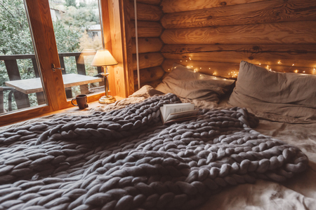 Rustic interior decoration of log cabin bedroom. Cozy warm blanket on bed by window. Stock Photo