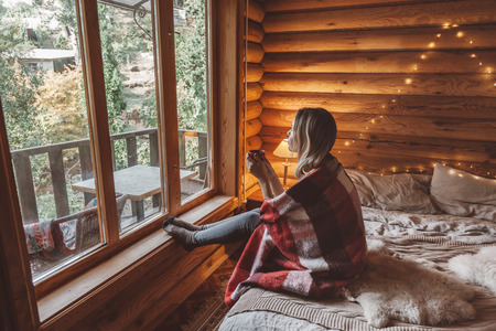 Woman in warm blanket relaxing and drinking morning coffee on cozy bed in log cabin in winter 免版税图像