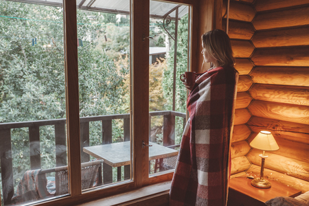 Woman in warm blanket relaxing and drinking morning coffee on cozy bed in log cabin in winter Reklamní fotografie