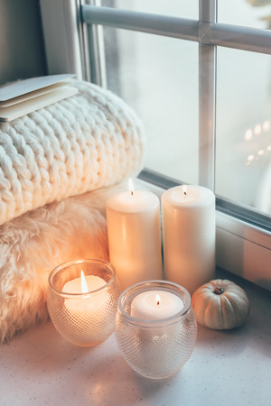 Warm and cosy hygge concept with white sweater and candles on a windowsill