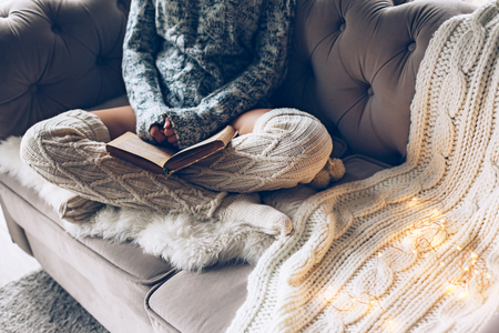 Cold autumn or winter weekend while reading book. Lazy day in warm knit clothing on the couch. Cosy scene, hygge concept.