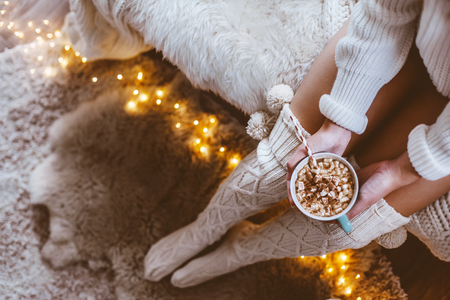 Cold autumn or winter weekend while drinking warm cocoa with marshmellows. Lazy day in knitted socks on the couch. Cosy scene, hygge concept, top veiw.